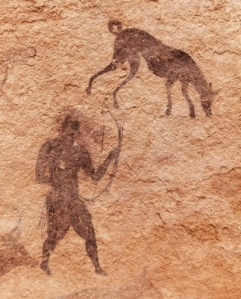 paleo man and dog working together